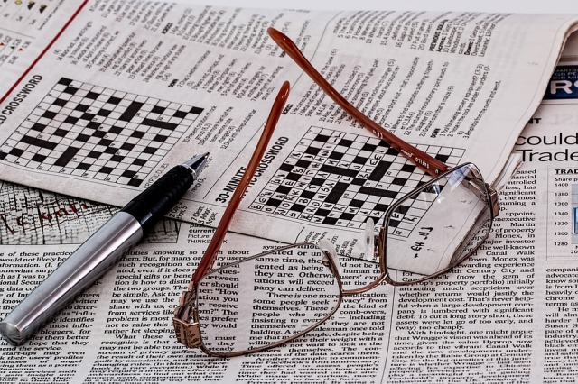 Picture of newspaper with crossword puzzle and glasses and pen lying on top