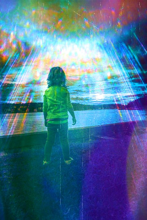child standing in front of a body of water, looking out at sunset with rays of light showering down
