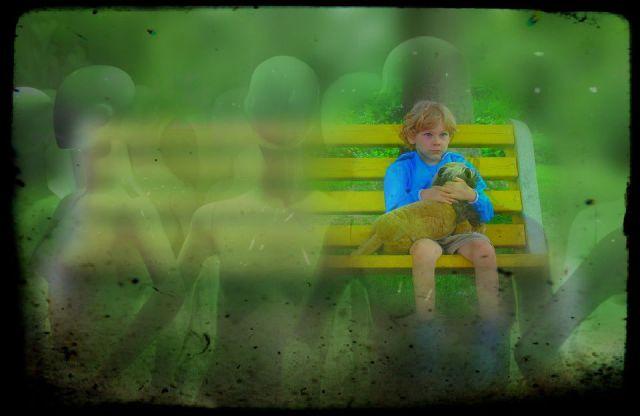 boy sitting alone female mannequins behind