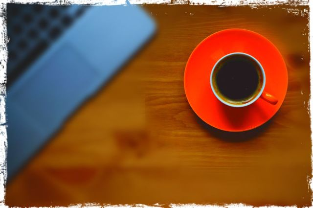 overhead view of cup of coffee beside laptop keyboard on a wooden table