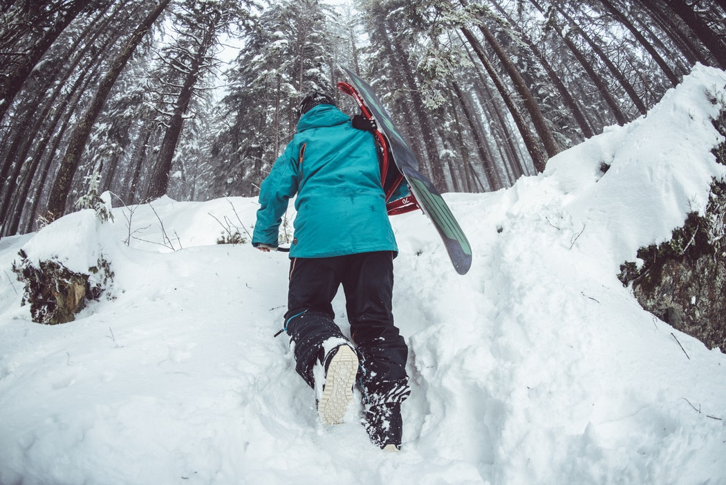person climbing up hill through snow carrying a snowboard
